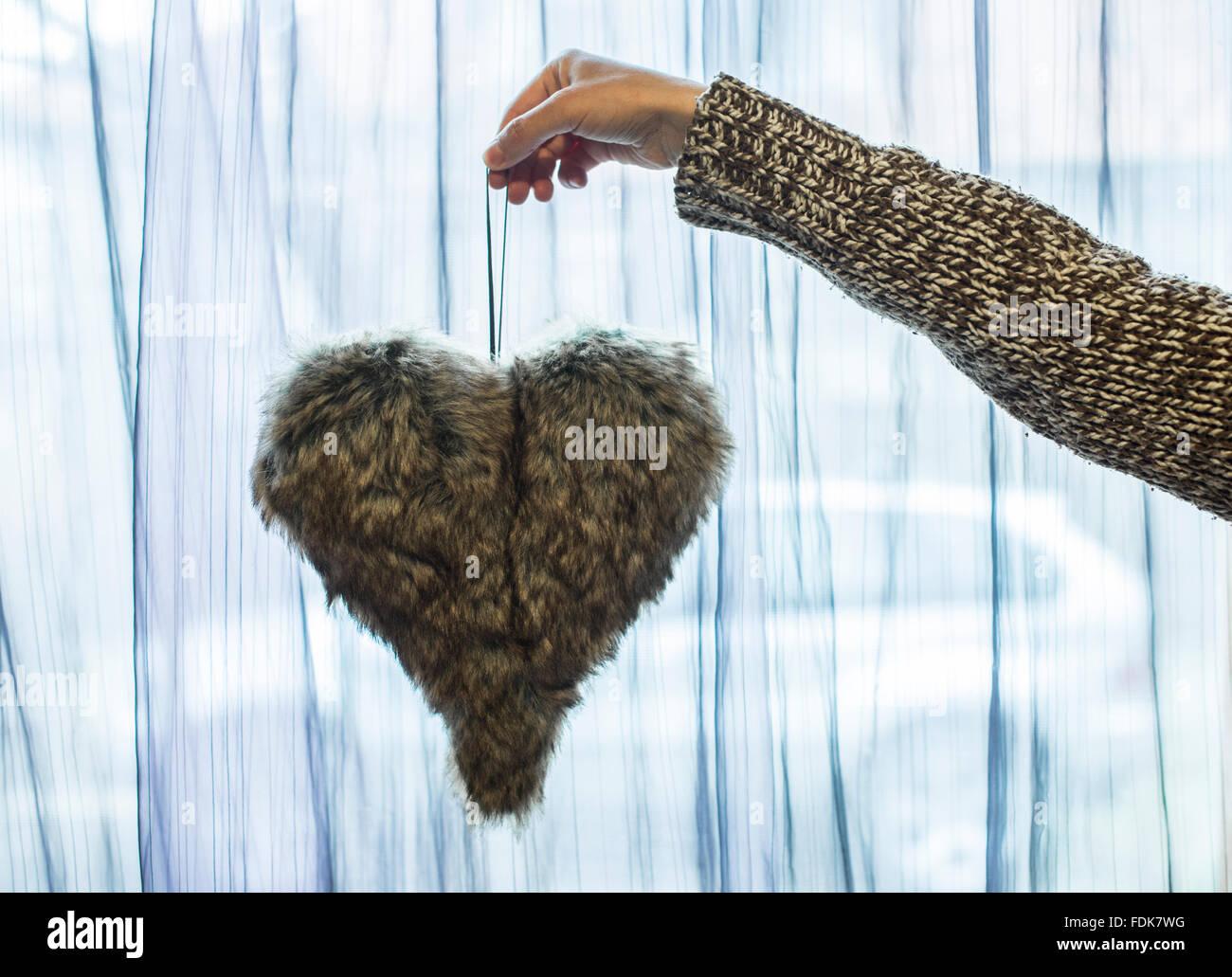 Mano sujetando peludo corazón decoración Imagen De Stock