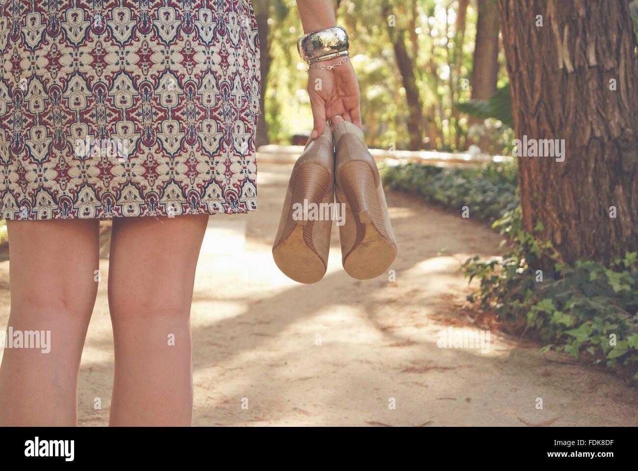 Vista trasera de una mujer sosteniendo par de zapatos. Foto de stock