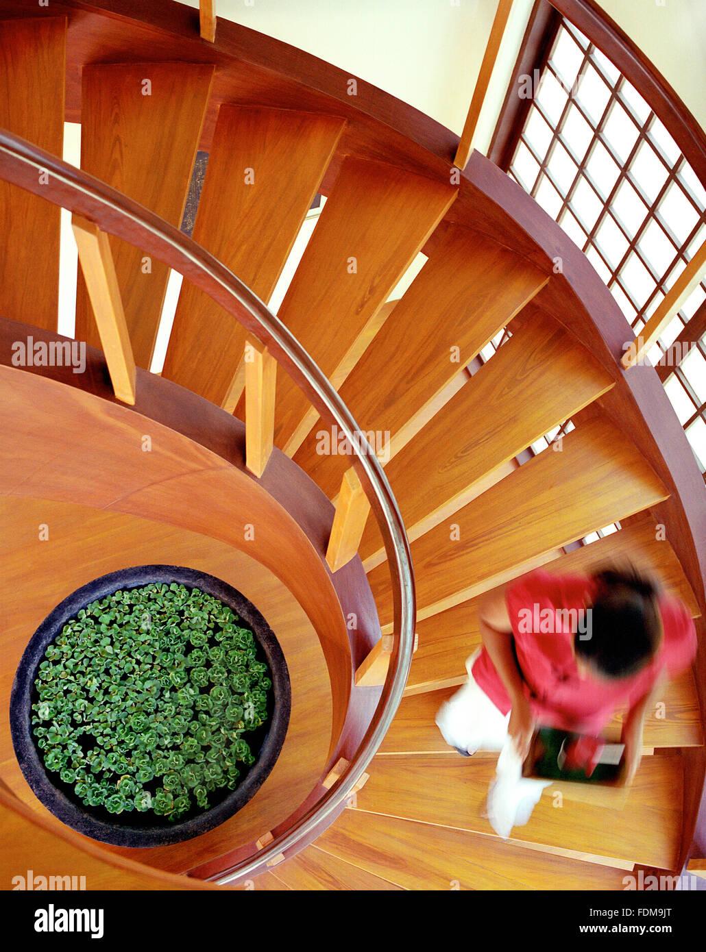 Una camarera lleva una bebida bajando una escalera en espiral dentro de Prana restaurante Mandala Spa. Isla de Boracay, Imagen De Stock