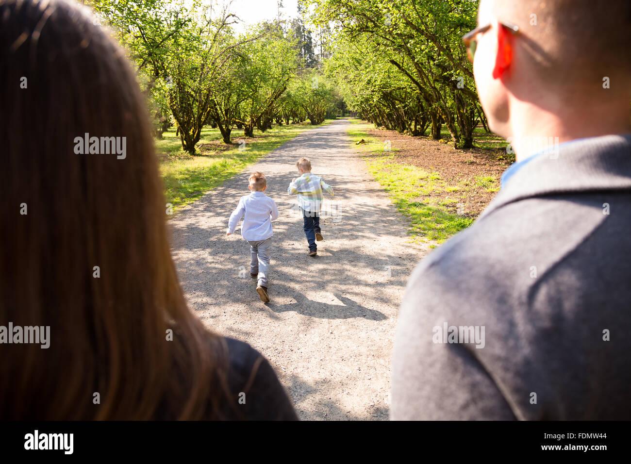 Una familia de cuatro, al aire libre en un entorno natural con buena luz en un retrato en el estilo de vida. Imagen De Stock