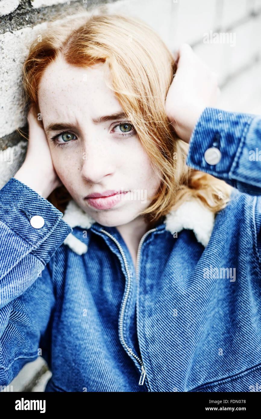 Tímida chica pelirroja, poniendo sus manos sobre sus oídos, retrato, Alemania Imagen De Stock