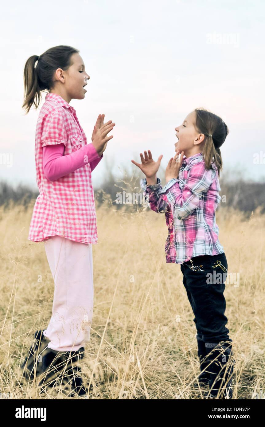 Las niñas en el campo tocando palmas juegos Imagen De Stock
