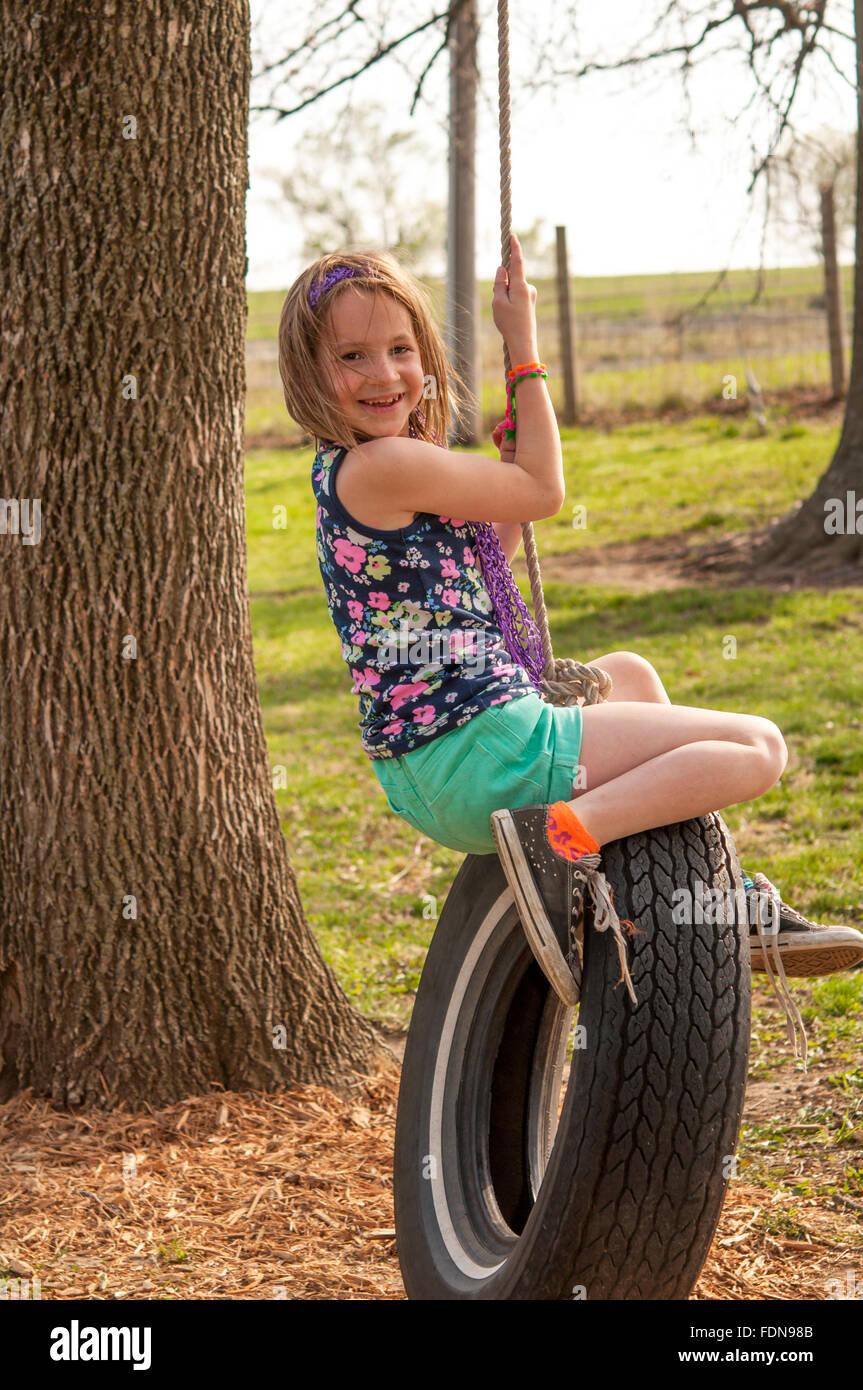Sonriente niña preadolescentes en el neumático swing Imagen De Stock