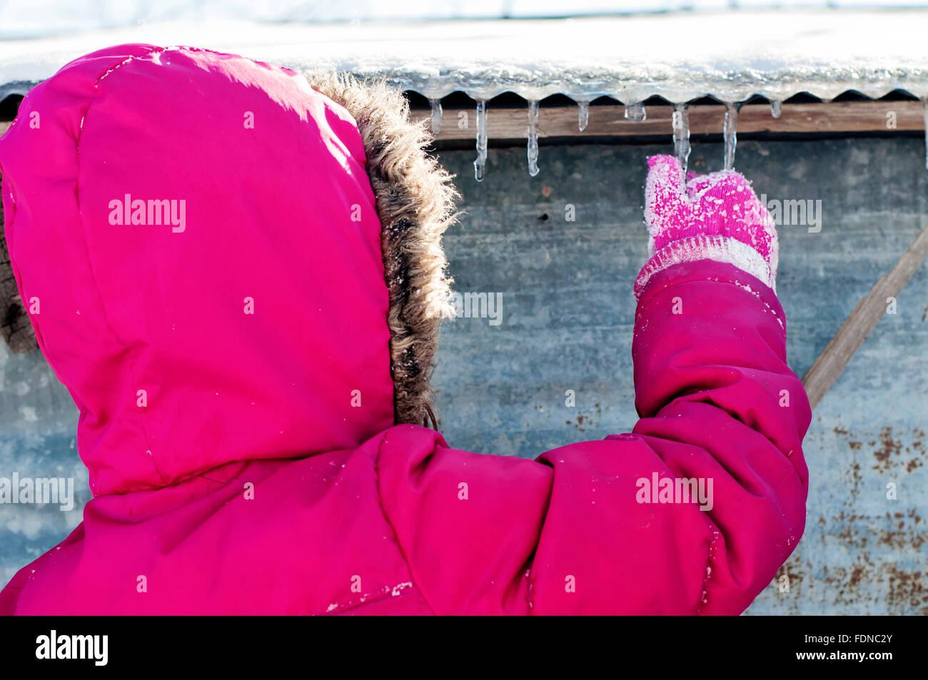 Niño en invierno escogiendo carámbanos de granero Imagen De Stock