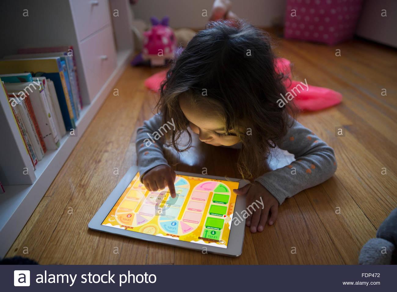 Chica jugando en tableta digital en el piso Imagen De Stock
