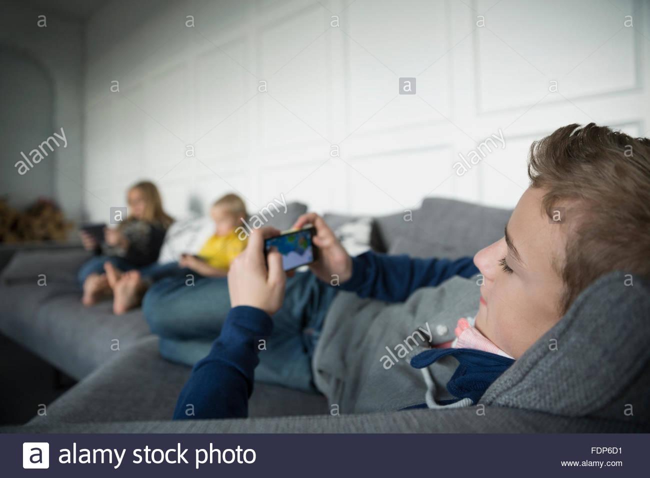 Niño jugando en el teléfono inteligente en el sofá Imagen De Stock