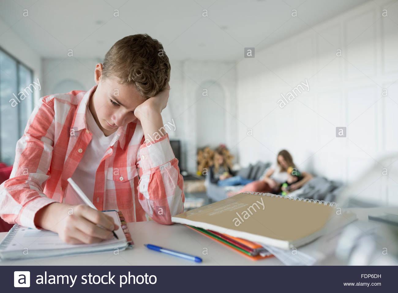 Cansado boy haciendo los deberes en la cocina Imagen De Stock