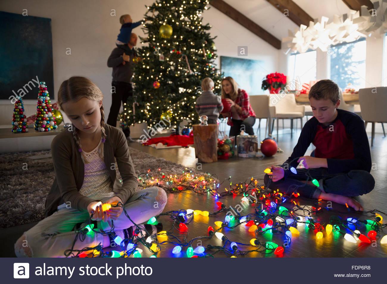 Hermano y hermana desenredar el árbol de navidad luces de cadena Imagen De Stock