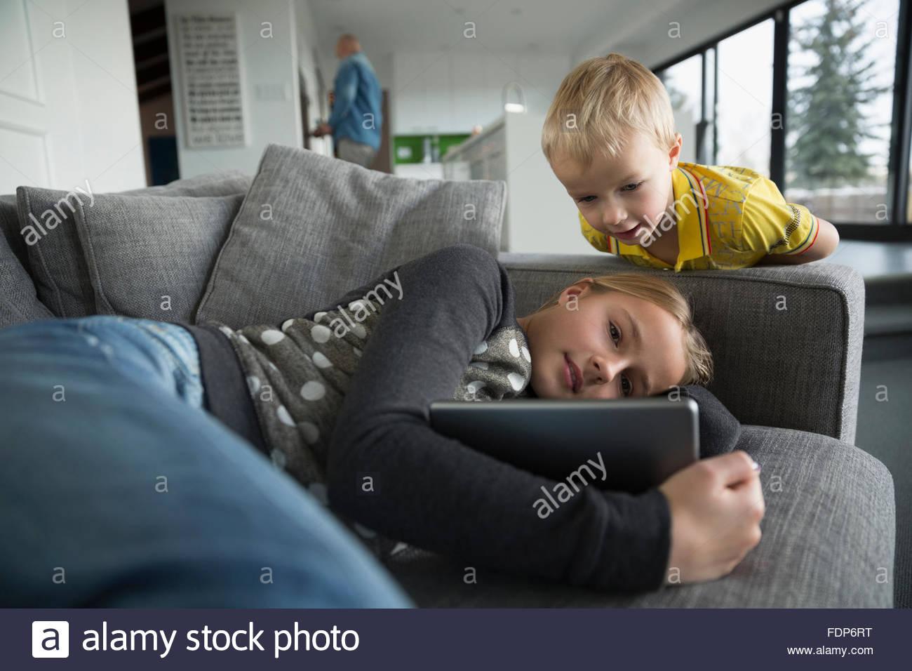 Hermano y hermana viendo la tableta digital en el sofá Imagen De Stock