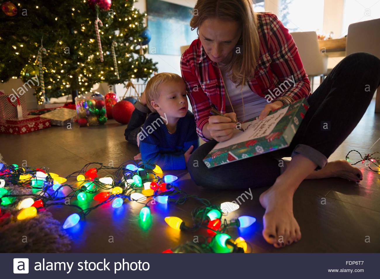 Madre e hijo haciendo lista navidad luces de cadena Imagen De Stock