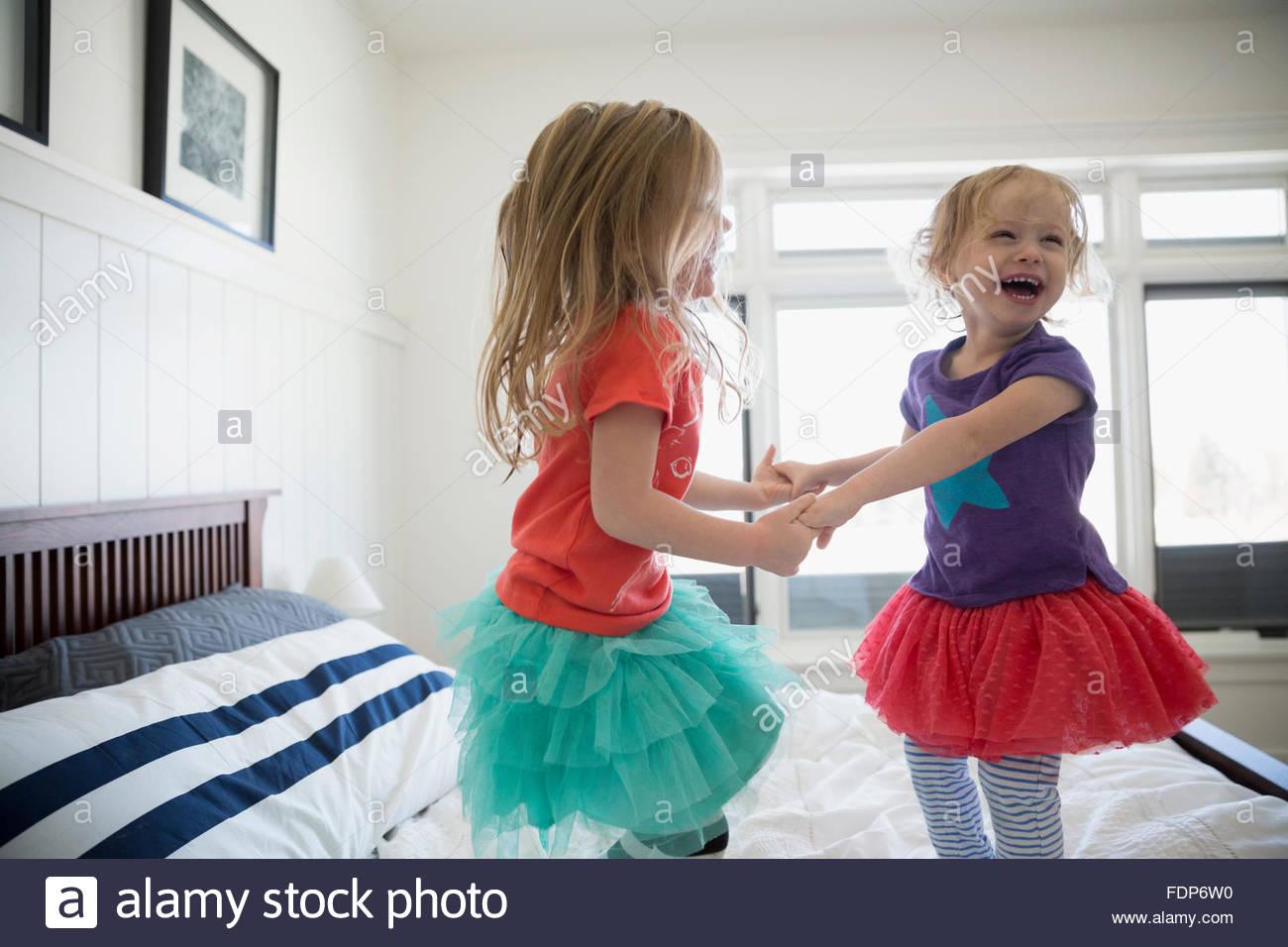 Juguetón hermanas tomados de la mano y saltar en la cama Imagen De Stock