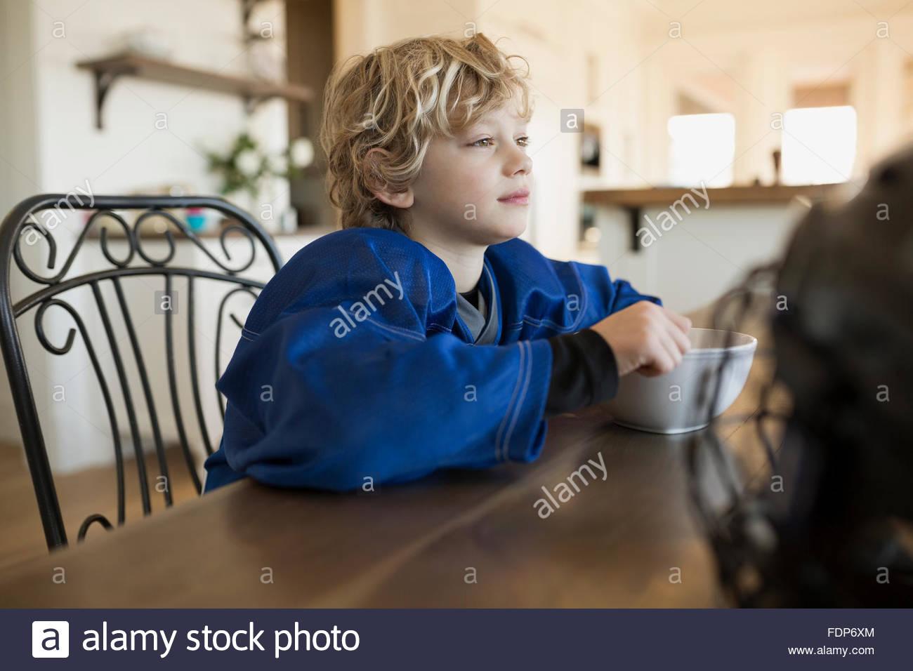 Pensativo boy comiendo cereal en la mesa Imagen De Stock