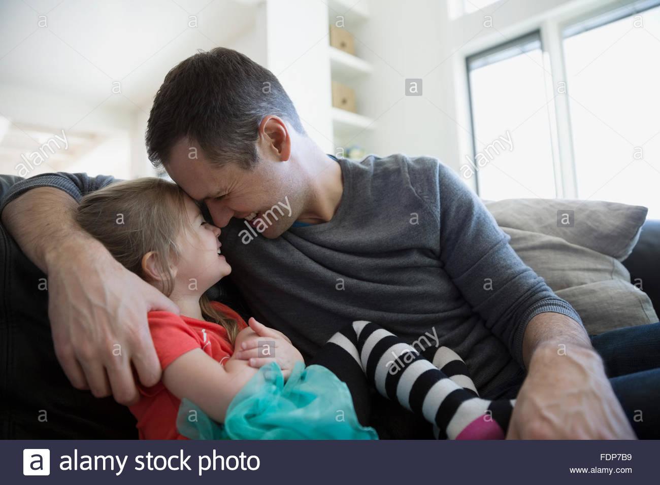 Afectuoso padre e hija frotando la nariz en el sofá Imagen De Stock