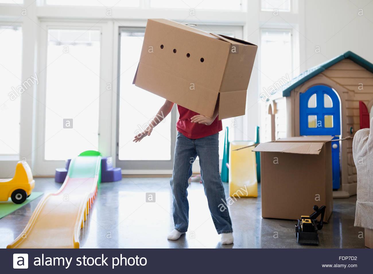 Muchacho juguetón bailando con caja de cartón en la cabeza. Imagen De Stock
