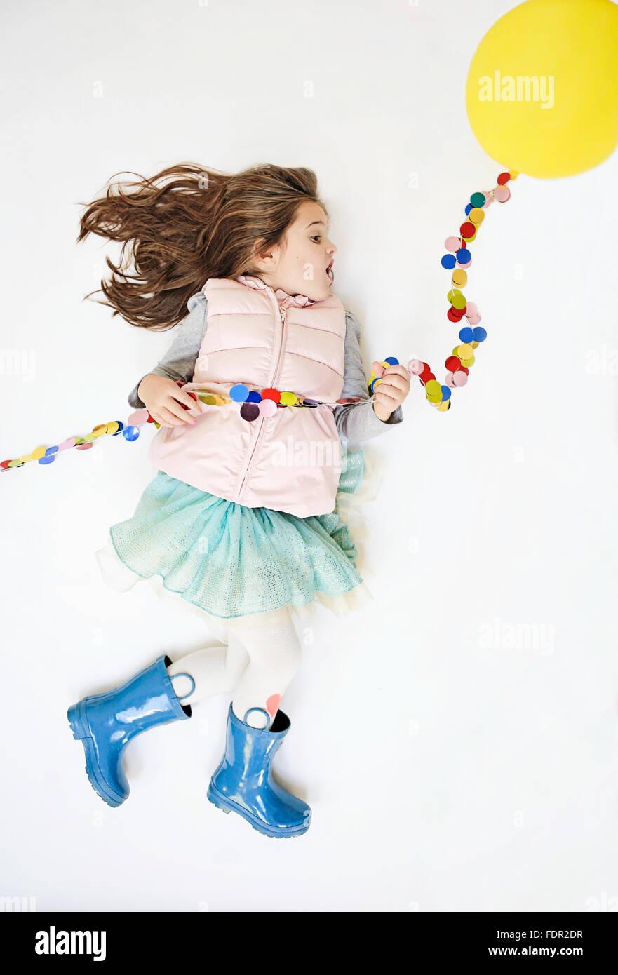 Little Girl fingiendo tomar vuelo por medio de un globo amarillo. Foto de stock