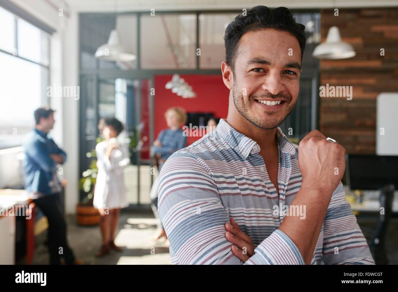 Retrato de smart profesional creativo mirando a la cámara y sonriendo. Feliz hombre de pie en caucásicos Imagen De Stock