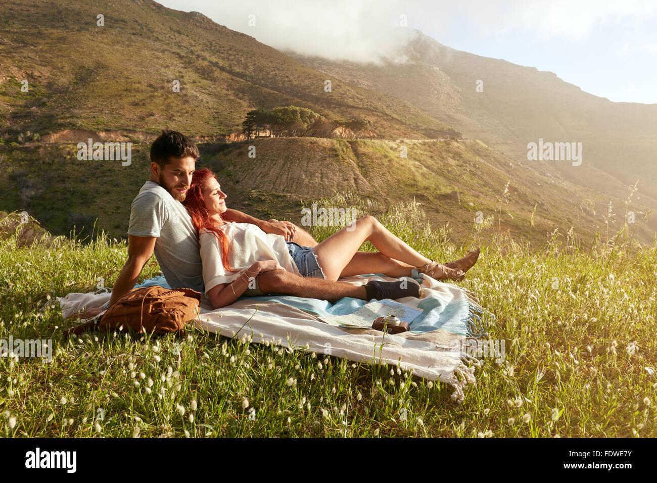 Feliz pareja joven en manta para picnic. Ellos son relajantes junto en un día de verano. Imagen De Stock