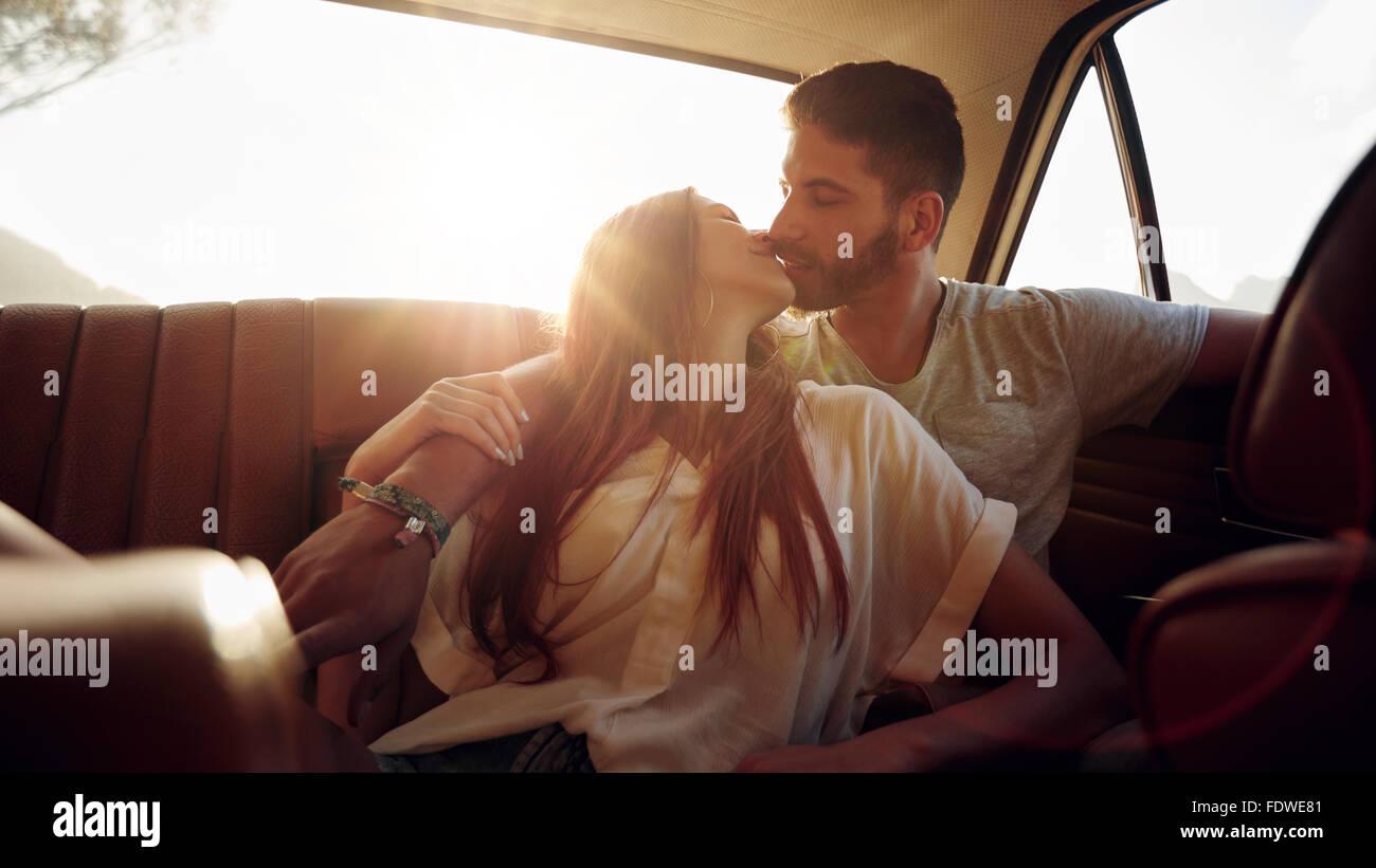 Romántica pareja joven sentado en el asiento de atrás de un coche y besos . Par afectuoso en el asiento Imagen De Stock
