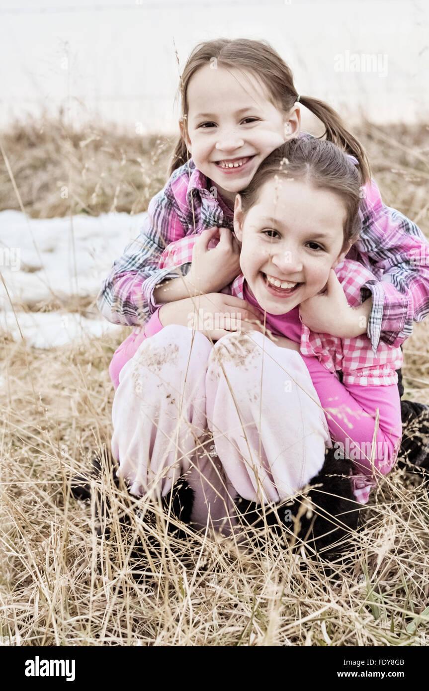 Dos hermanas sonriente abrazando en el campo País Imagen De Stock