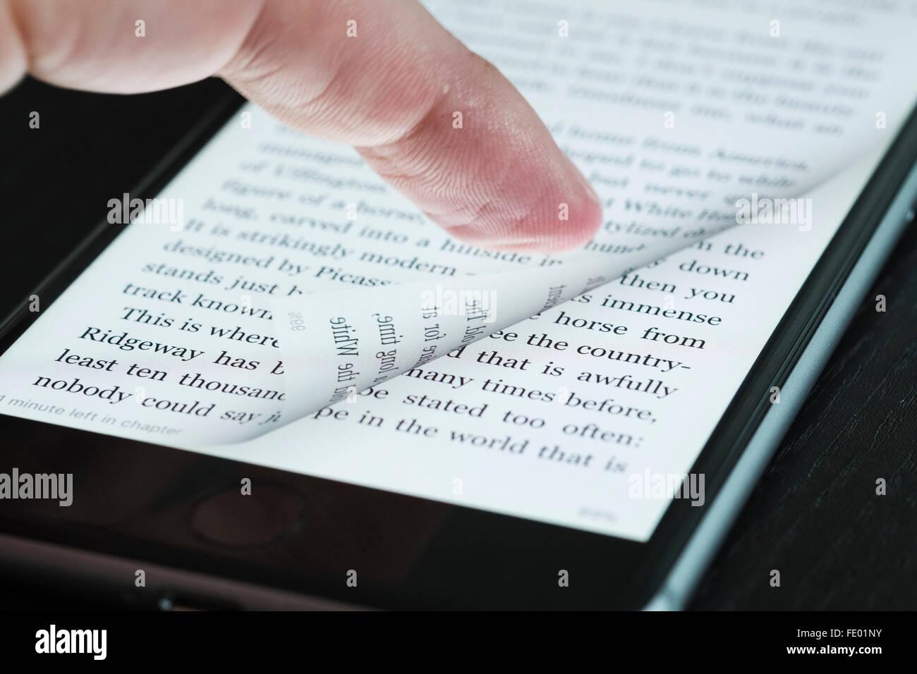 Girar página de ebook con dedos en un iPhone 6 más teléfonos inteligentes. Imagen De Stock