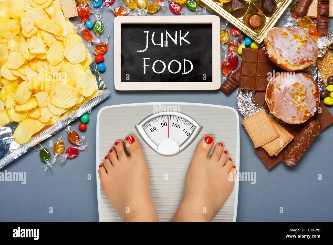 Las dietas malsanas, el sobrepeso. Pies en báscula de baño Imagen De Stock