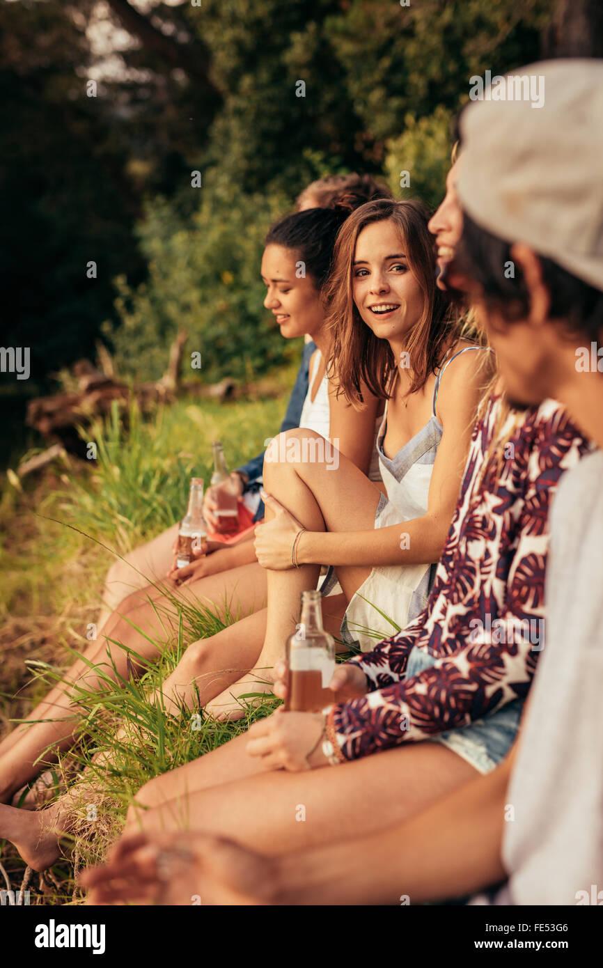 Retrato de mujer joven sentada con sus amigos por un lago. Los jóvenes que cuelgan en el lago. Imagen De Stock