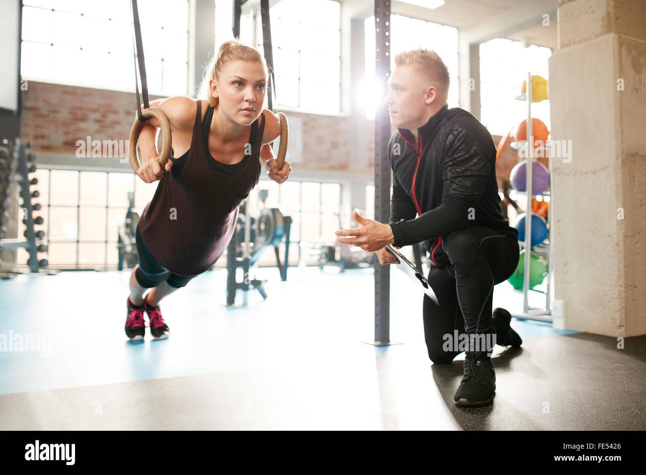 Mujer joven está haciendo ejercicios con la ayuda de un entrenador personal en un gimnasio moderno. Trabajo Imagen De Stock