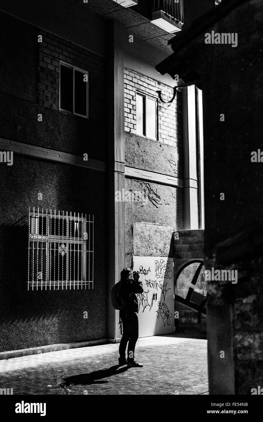 Vista trasera del fotógrafo en un callejón de la ciudad contra la construcción Foto de stock