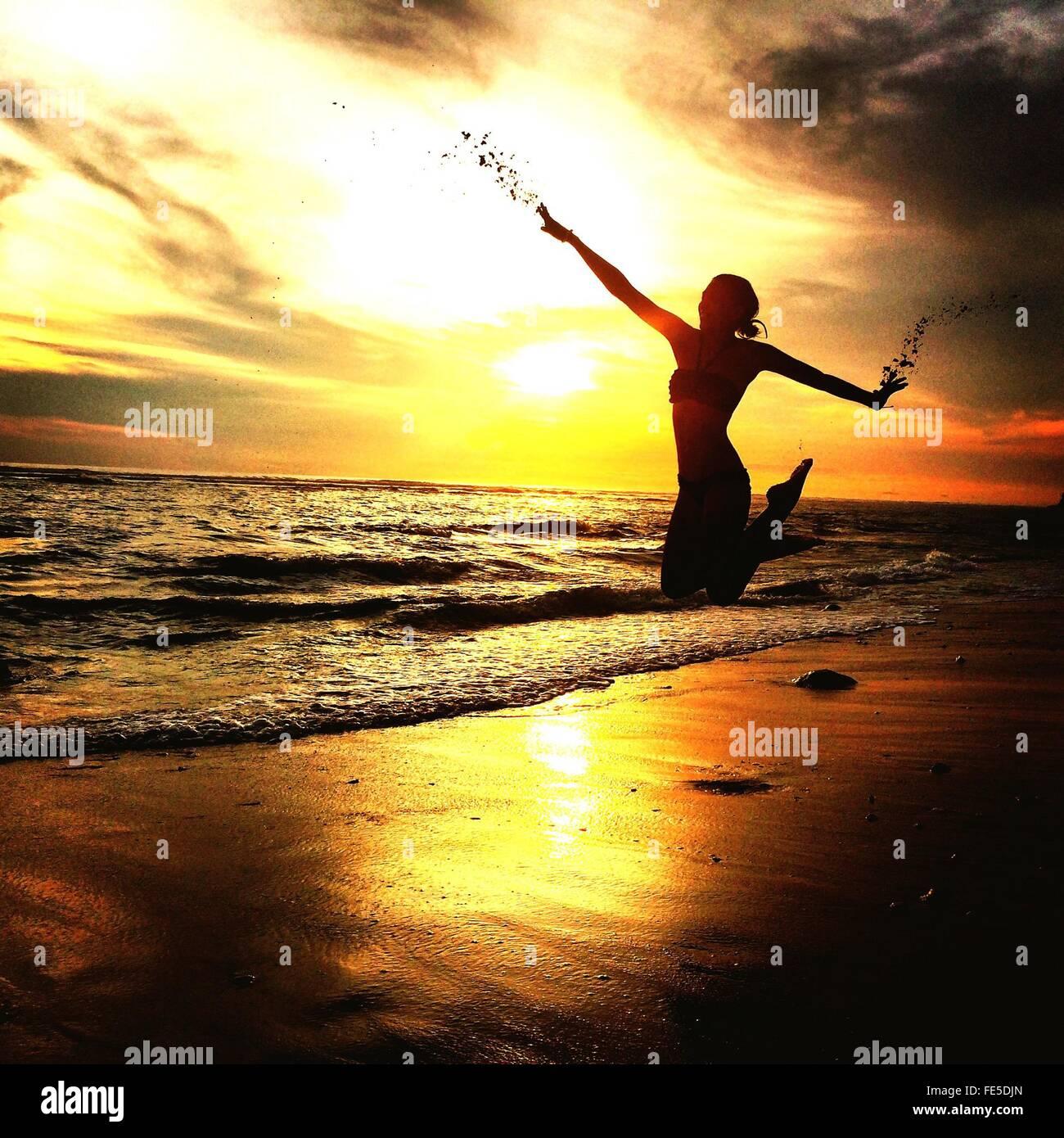 Mujer saltando en la playa de arena durante la puesta de sol Imagen De Stock