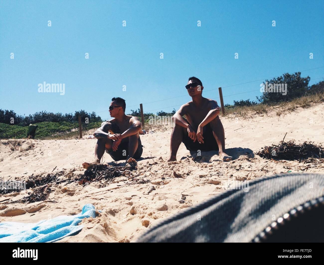 Ángulo de visión baja de amigos relajándose en la playa de arena Imagen De Stock
