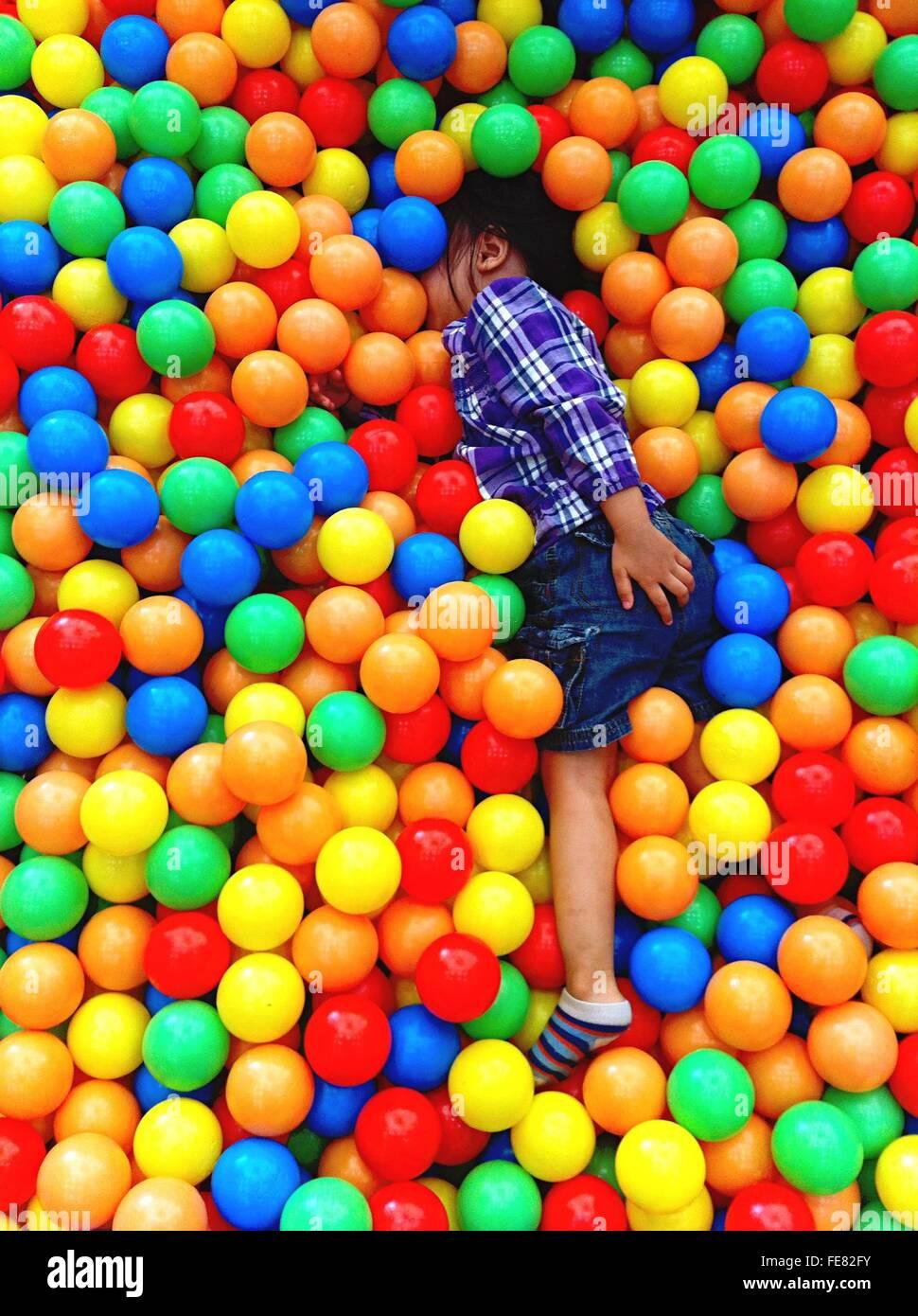 Un alto ángulo de visualización del niño jugando en la piscina de bolas Foto de stock