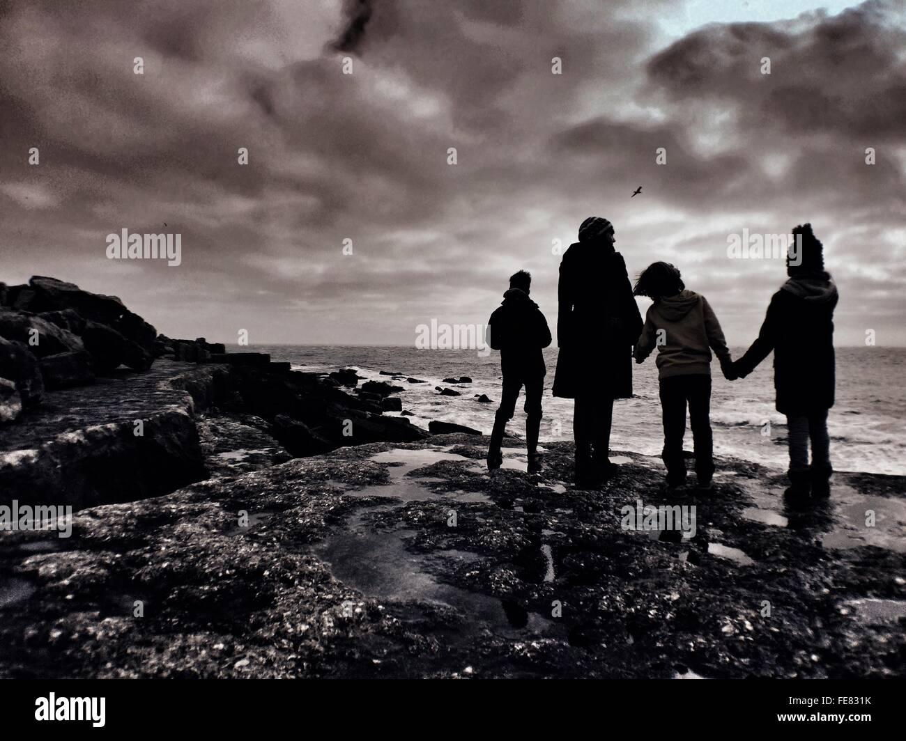 Silueta de la familia en la playa de la costa de permanente Imagen De Stock