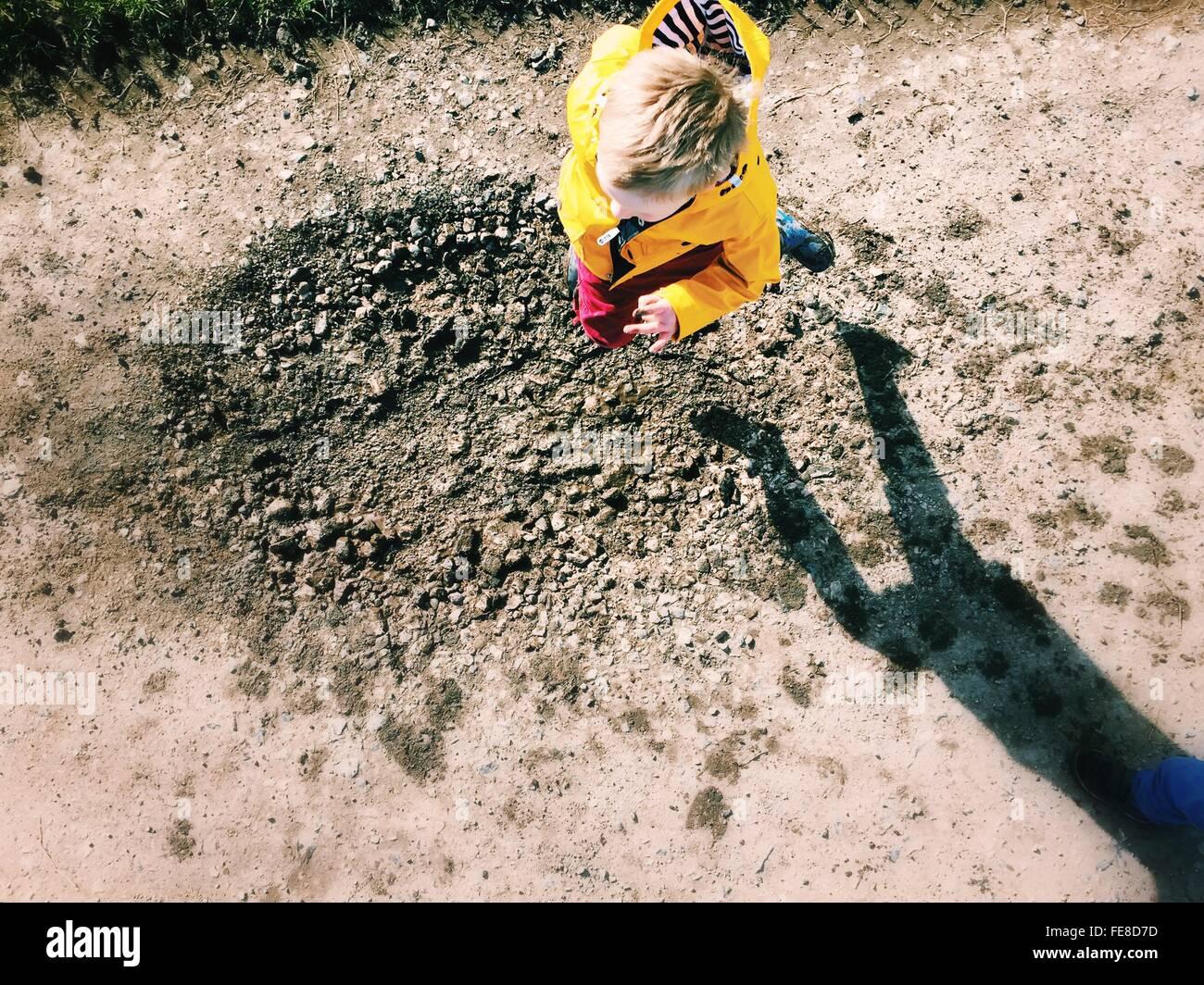 Un alto ángulo de visualización de Boy saltar sobre charcos de barro Imagen De Stock