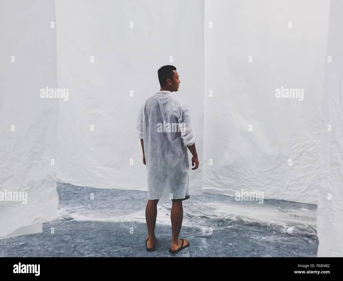 Vista trasera de la longitud completa de hombre de pie contra la pared blanca Imagen De Stock