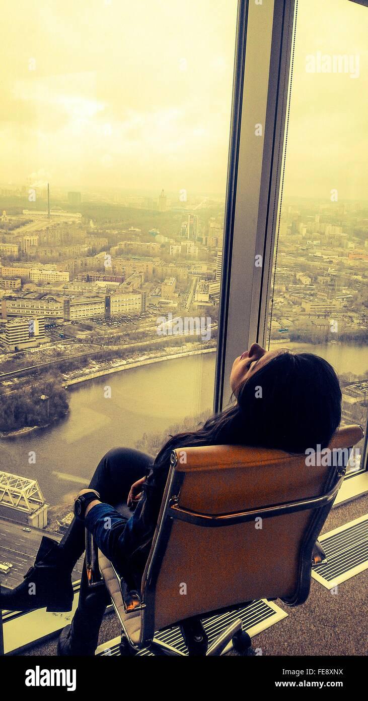 Pisado mujer de negocios sentada en una silla delante de la ventana de la Oficina en la ciudad Imagen De Stock