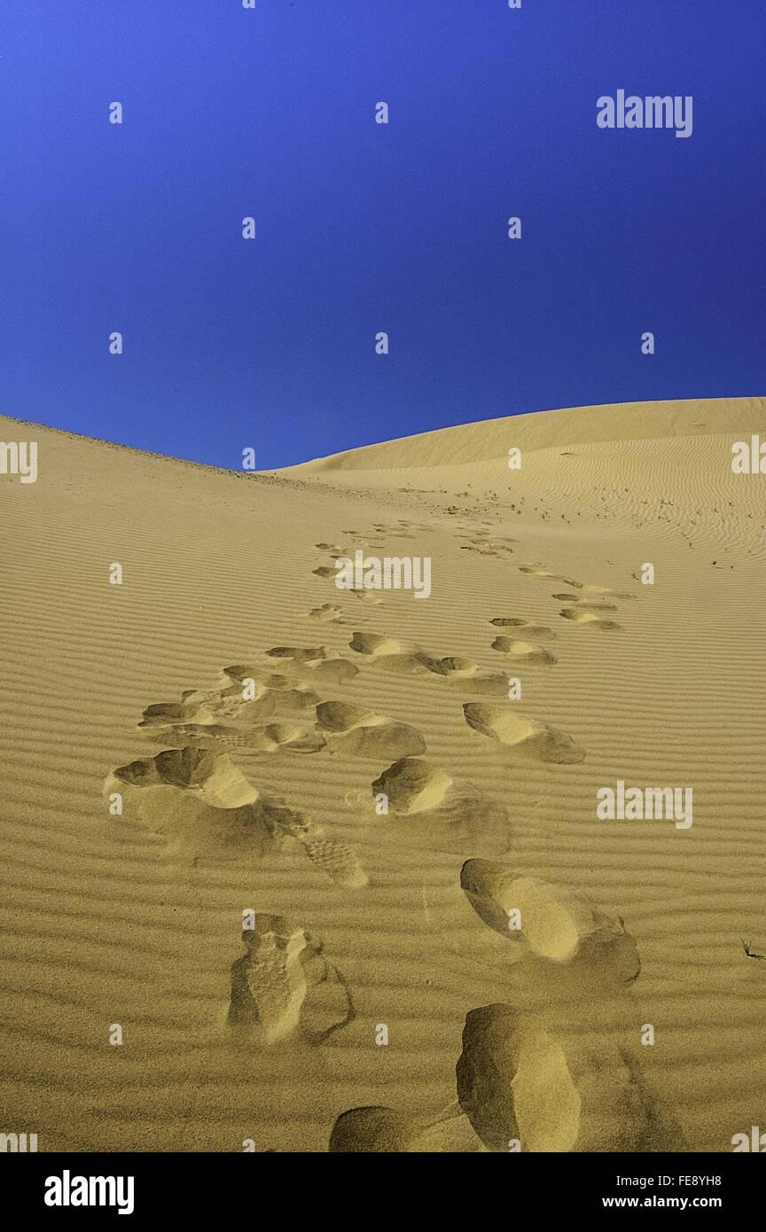 Huellas en el desierto contra el cielo azul claro Imagen De Stock