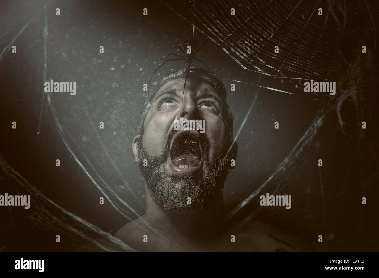 El hombre con la boca abierta mirando Spider contra fondo negro Imagen De Stock