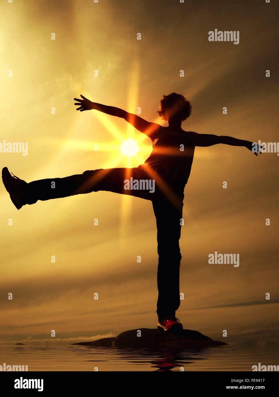 Boy ejercer sobre una roca en el mar contra el cielo durante la puesta de sol Imagen De Stock