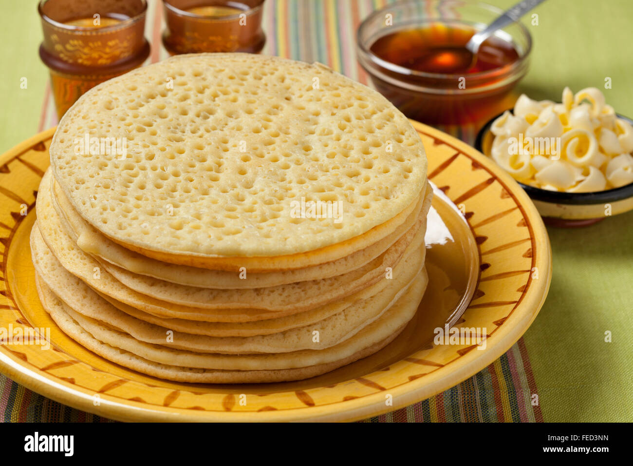 Montón de tortitas beghrir marroquíes tradicionales servidos con miel y mantequilla. Imagen De Stock