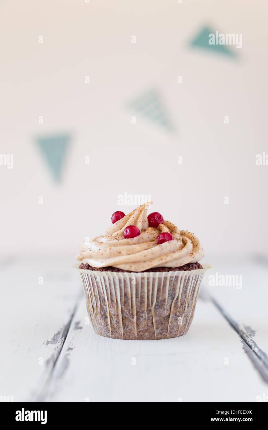 Cumpleaños cupcake un fondo de madera blanca y un día de nacimiento streamer Imagen De Stock