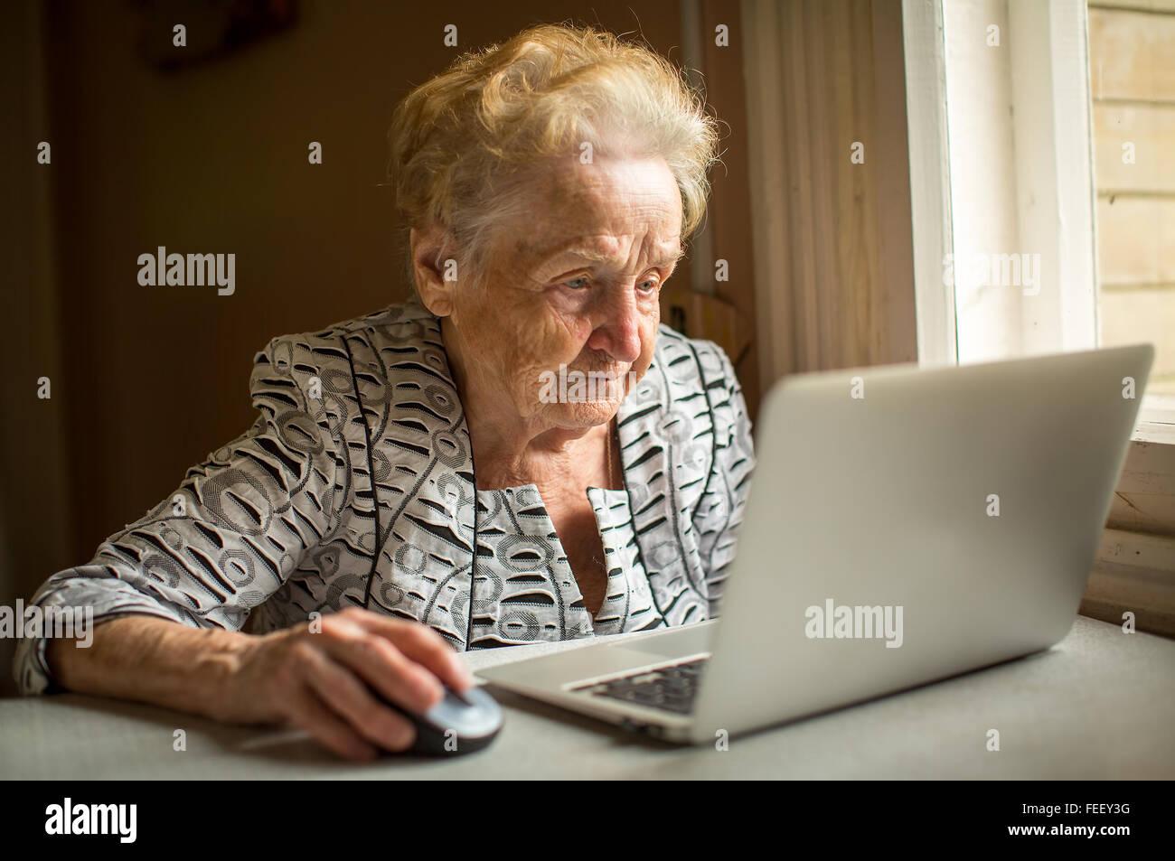 Anciana trabajando en el portátil en casa sentados a la mesa. Imagen De Stock