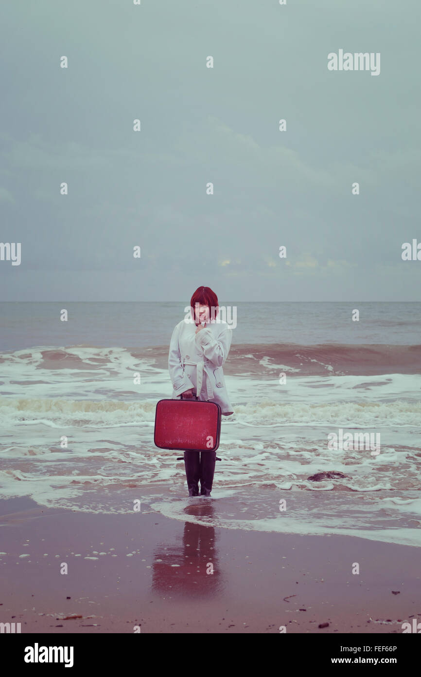Una mujer en una bata blanca con una maleta roja en el mar en invierno Foto de stock