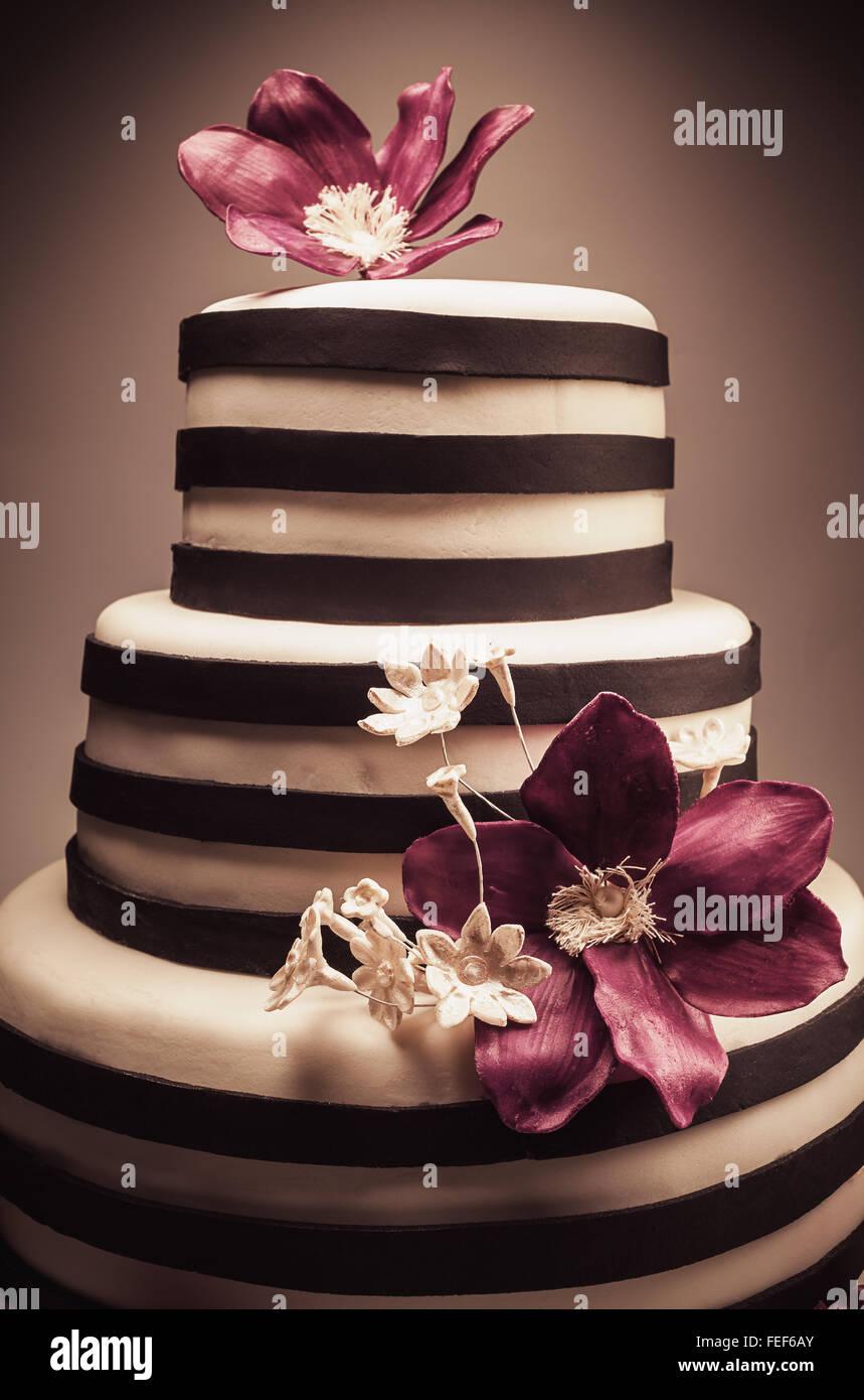 Detalles de una boda o un pastel de cumpleaños, tamaño triple, en el estudio sobre fondo blanco. Violeta Imagen De Stock