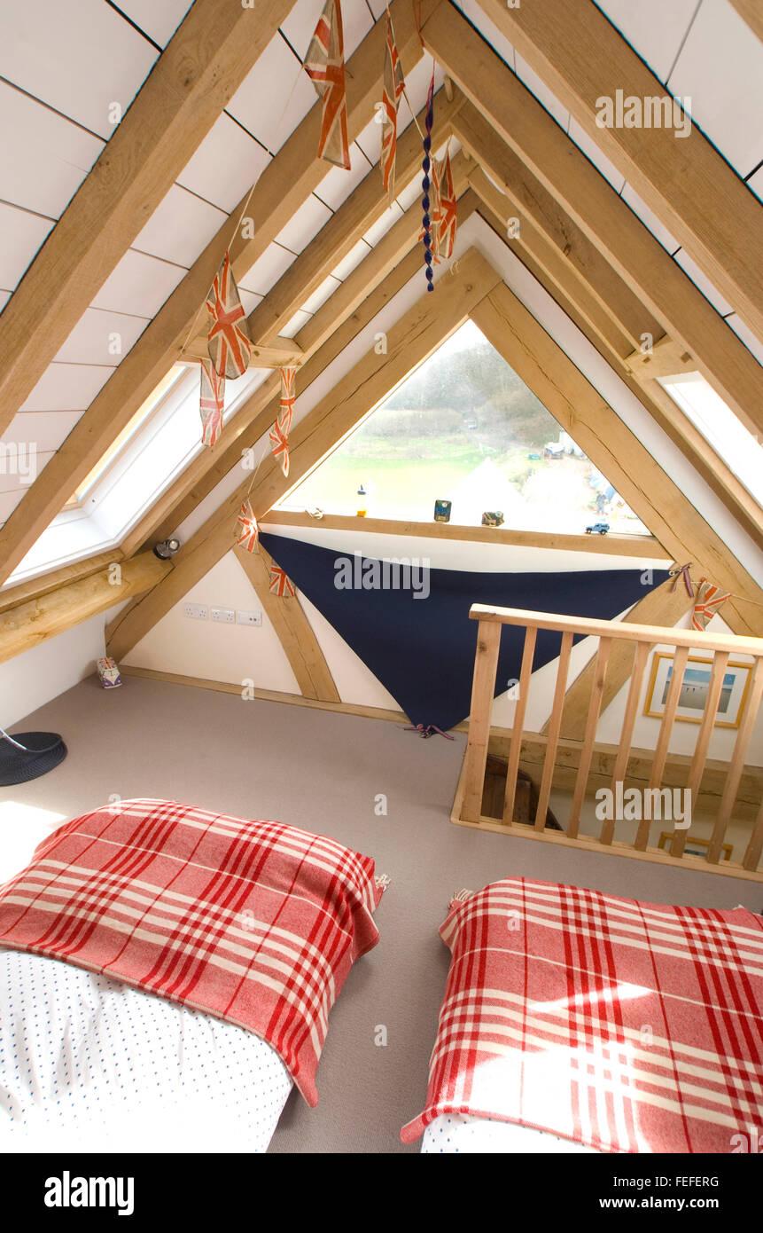 Habitación abuhardillada para niños, las vigas de roble y pintura blanca, con dos camas. Imagen De Stock