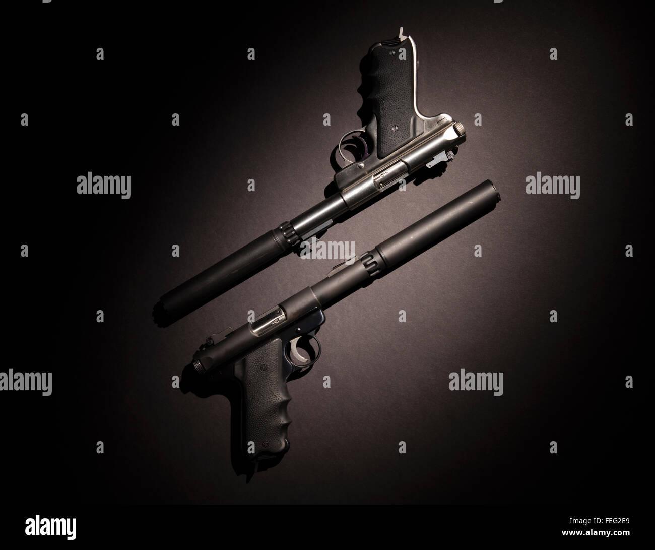 Dos pistolas semiautomáticas con silenciadores sobre fondo negro. Imagen De Stock