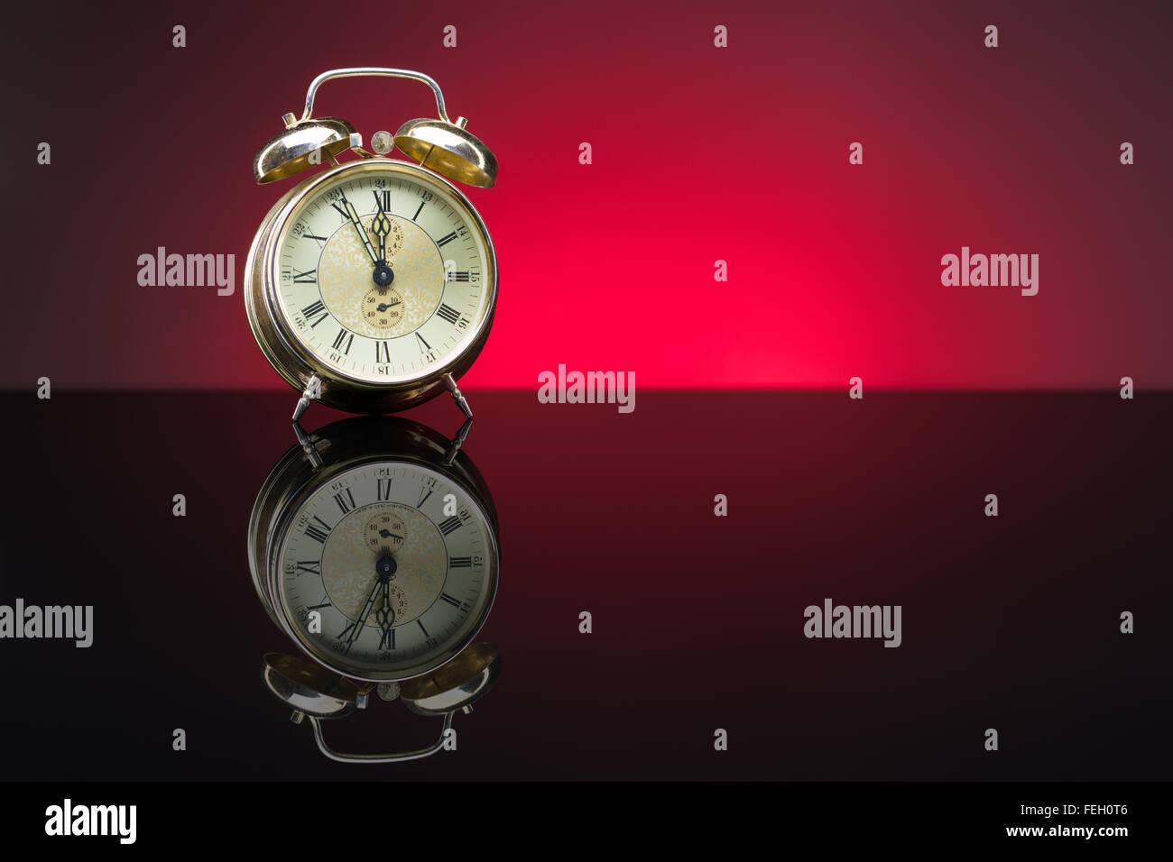 Vintage despertador mostrando cinco minutos a doce, fondo rojo, espacio de copia Foto de stock