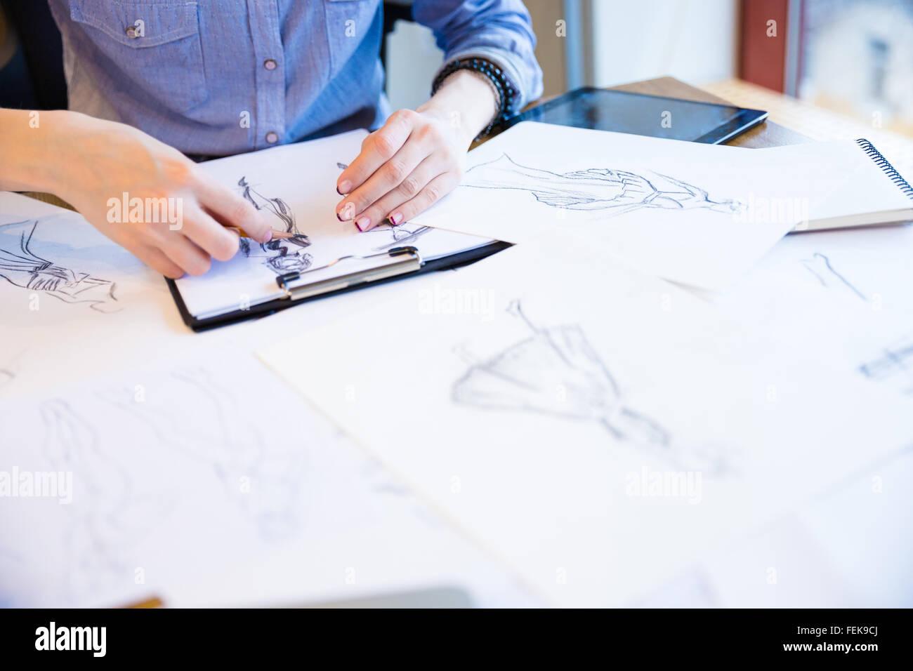 Acercamiento de las manos del joven diseñador de moda crear nueva colección de ropa y dibujar bocetos en portapapeles Foto de stock