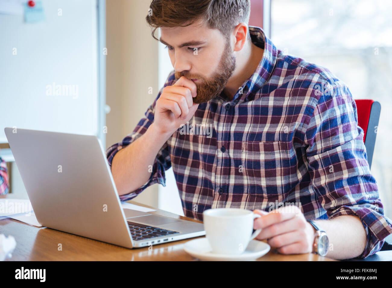 Grave joven barbudo centrado en camisa a cuadros sentado en la mesa y utilización portátil Imagen De Stock