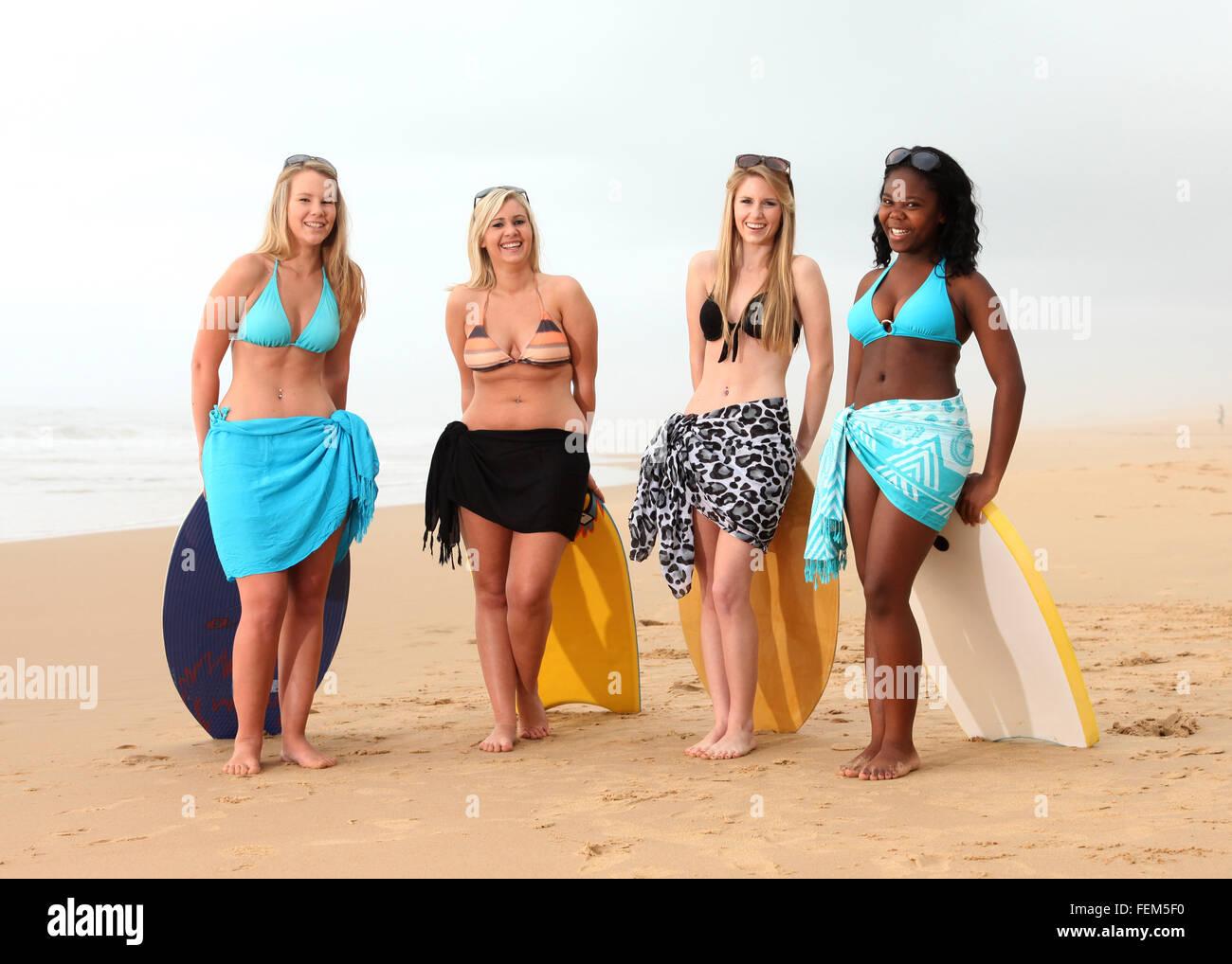 Un Grupo De Cuatro Amigas Están De Pie Con Sus Tablas De Surf O