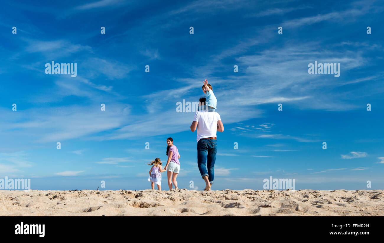 Una familia de cuatro, caminar hacia la costa. El chico está en la espalda de los padres y se mece en la cámara. Imagen De Stock